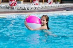Szczęśliwa dziewczyna z piłką w pływackim basenie fotografia stock