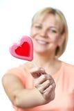 Szczęśliwa dziewczyna z serce kształtnym lizakiem Zdjęcia Royalty Free