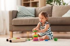 Szczęśliwa dziewczynka bawić się z zabawka blokami w domu obraz stock