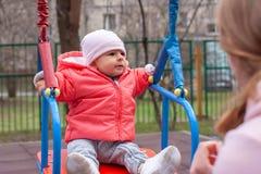 Szczęśliwa dziewczynka w różowej kurtce i biały kapeluszowy chlanie w huśtawkach drewna i żelaza Przed matką pogodna dzie? wiosna obraz stock