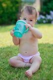 Szczęśliwa dziewczynka w spodnie wodzie pitnej butelka, siedzi Obrazy Stock