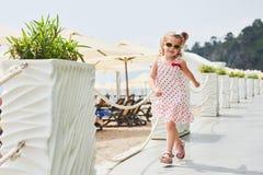 Szczęśliwa dziewczynka w sukni na plaży morzem w lecie Obrazy Royalty Free