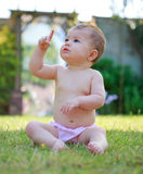 Szczęśliwa dziewczynka wskazuje up w spodniach, siedzący na trawie Fotografia Stock