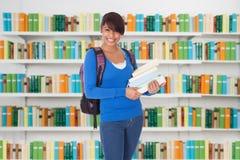 Szczęśliwa Żeńska student uniwersytetu pozycja W bibliotece Zdjęcia Stock