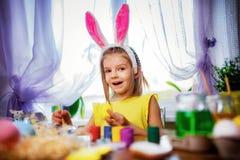 Szczęśliwa Easter dziewczyna w królików ucho maluje jajka, mały dziecko w domu Wiosna wakacje obraz royalty free