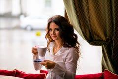 Szczęśliwa elegancka brunetki kobieta z kędzierzawą długie włosy pije kawą w kawiarni i ono u?miecha si? zdjęcie royalty free