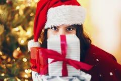 Szczęśliwa elegancka kobieta trzyma wiele prezentów pudełka z bo w Santa kapeluszu Zdjęcie Royalty Free