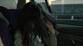 Szczęśliwa figlarnie mała dziewczynka w samochodzie przy dziecka siedzeniem bawić się z jej włosy zbiory
