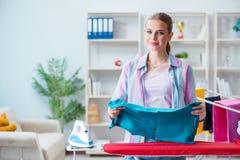Szczęśliwa gospodyni domowa robi odprasowywać w domu Obraz Stock