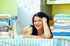 Szczęśliwa gospodyni domowa uzupełniający prasowanie, domowy wnętrze obraz stock