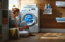 Szczęśliwa gospodyni domowej kobieta w pralnianym pokoju z pralką obrazy stock