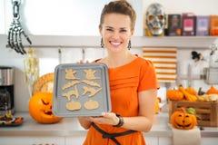 Szczęśliwa gospodyni domowej mienia taca uncooked Halloweenowi ciastka Zdjęcia Royalty Free