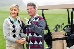 Szczęśliwa grać w golfa para z golfowym powozikiem behind Fotografia Stock