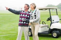 Szczęśliwa grać w golfa para z golfowym powozikiem behind Zdjęcia Stock