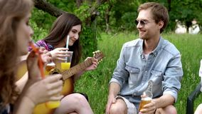 Szczęśliwa grupa przyjaciel otuchy podczas gdy bawić się gitarę outside zbiory wideo