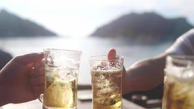 Szczęśliwa grupa przyjaciele wznosi toast z szkłem piwo w plażowej kawiarni Otuchy sukces swobodny ruch 3840x2160 zbiory
