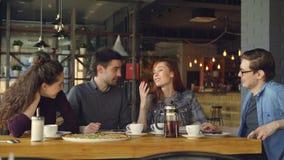 Szczęśliwa i atrakcyjna grupa przyjaciele jest gawędząca wpólnie i roześmiana w małym domu kawiarni lub pizzy zbiory