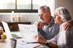 Szczęśliwa i czułość starej pary czytelnicza gazeta przy kuchnią obrazy stock