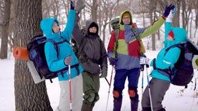 Szczęśliwa i niepłonna grupa wycieczkowicze stawia ich ręki wpólnie po środku zima lasu, budynek zbiory