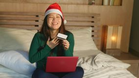 Szczęśliwa i piękna Azjatycka Amerykańska dziewczyna w Santa Bożenarodzeniowej kapeluszowej używa karcie kredytowej i laptop dla  zdjęcie wideo