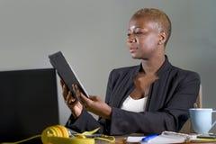Szczęśliwa i pomyślna czarna afro Amerykańska biznesowa kobieta pracuje przy nowożytnym biurowym ono uśmiecha się rozochoconym uż Obrazy Stock