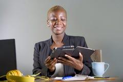 Szczęśliwa i pomyślna czarna afro Amerykańska biznesowa kobieta pracuje przy nowożytnym biurowym ono uśmiecha się rozochoconym uż Zdjęcie Royalty Free