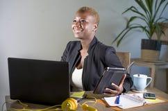 Szczęśliwa i pomyślna czarna afro Amerykańska biznesowa kobieta pracuje przy nowożytnym biurowym ono uśmiecha się rozochoconym uż Obrazy Royalty Free