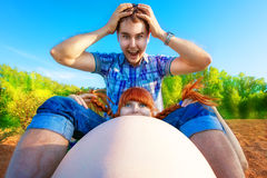 Szczęśliwa i potomstwa ciężarna para ma zabawę na plaży przy sunse Zdjęcia Stock