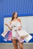 Szczęśliwa i uśmiechnięta młoda brunetka pozuje z torbami Pogodny i spopping dzień dziewczyna białe ubrania zdjęcie royalty free