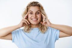 Szczęśliwa i zadowolona śliczna europejska blond kobieta trzyma ręki na twarzy z niebieskimi oczami tak jakby ono uśmiecha się w  obraz royalty free