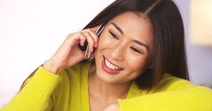 Szczęśliwa Japońska kobieta opowiada na smartphone obrazy royalty free