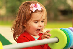 Szczęśliwa jeden roczniak dziewczyna bawić się z drewnianymi kolorowymi okręgami Fotografia Royalty Free