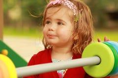 Szczęśliwa jeden roczniak dziewczyna bawić się z drewnianymi kolorowymi okręgami Zdjęcia Stock