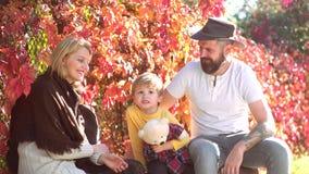 Szczęśliwa jesieni rodzina w miłości Szczęśliwi potomstwa wychowywają z dziecko chłopiec w jesień parku na pogodnym jesień dniu W zbiory wideo