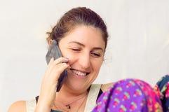 Szczęśliwa Kaukaska kobieta opowiada na jej telefonie komórkowym zdjęcia stock
