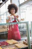 Szczęśliwa kelnerka w czerwonej fartuch ofiary babeczce fotografia stock
