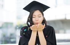 Szczęśliwa kończąca studia studencka dziewczyna dmucha multicolor confetti od go Obraz Royalty Free