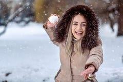 Szczęśliwa kobieta bawić się snowball walkę na śnieżnym dniu Zimy conce obrazy royalty free