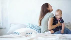 Szczęśliwa kobieta bawić się z jej dzieckiem na sypialni w dniu zbiory