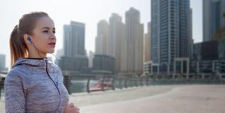 Szczęśliwa kobieta biega nad Dubai miastem z słuchawkami zdjęcia stock