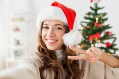 Szczęśliwa kobieta bierze selfie nad choinką fotografia royalty free