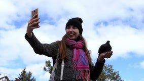 Szczęśliwa kobieta bierze selfie z gołąbką w jej ręce w mo zbiory