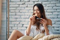Szczęśliwa kobieta cieszy się aromat kawę w łóżku po budzi się obrazy royalty free
