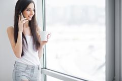 Szczęśliwa kobieta cieszy się homey ranek Atrakcyjna młodej kobiety pozycja blisko nadokiennego, pijący kawy od bielu lub herbaty obrazy stock