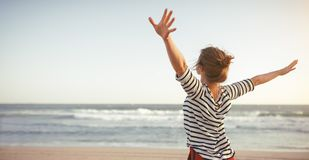 Szczęśliwa kobieta cieszy się wolność z otwartymi rękami na morzu