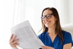 Szczęśliwa kobieta czyta gazetę przy biurem w szkłach Fotografia Royalty Free