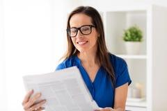 Szczęśliwa kobieta czyta gazetę przy biurem w szkłach Fotografia Stock