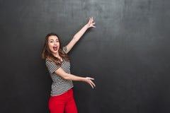 Szczęśliwa kobieta demonstruje coś Obrazy Stock