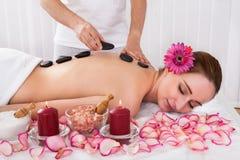 Szczęśliwa kobieta dostaje gorącą kamienną terapię Fotografia Stock