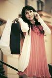 Szczęśliwa kobieta dzwoni na telefonie z torba na zakupy Zdjęcia Royalty Free